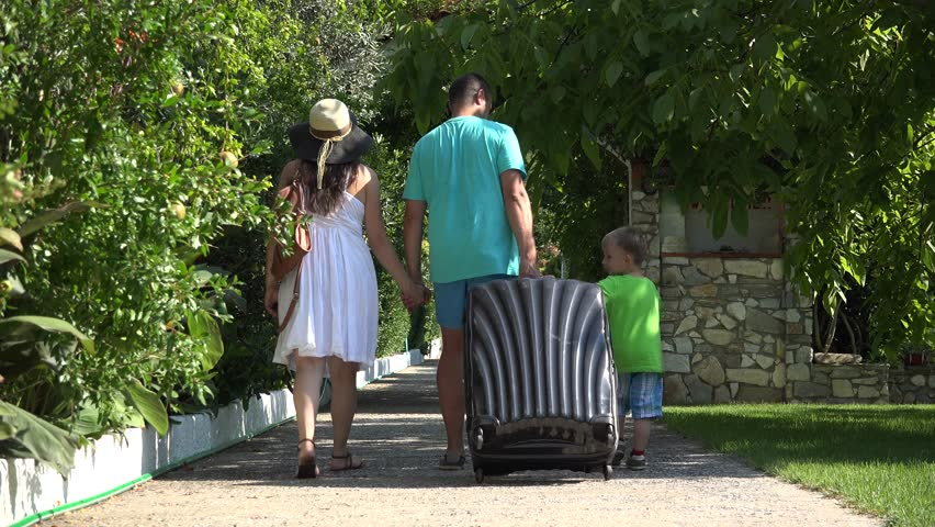 Young family with big suitcase walking on green alley to holiday place | Shutterstock HD Video #17176816
