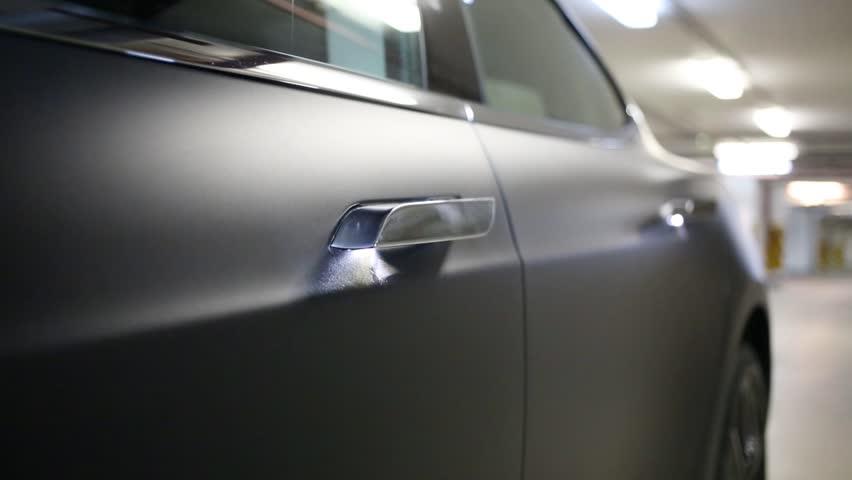 Woman hand opens black car door in parking, shallow dof