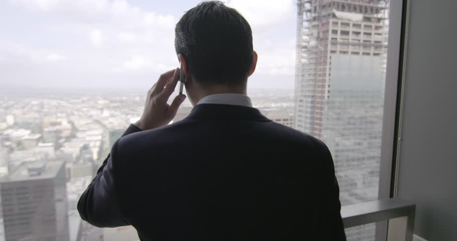 Successful young business man using a cellphone in front of a skyscraper window with views across Los Angeles.  Medium close up, rear view, dolly shot originally recorded in 4K