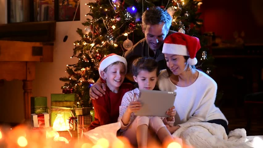 Christmas night, a cheerful family of four people under the Christmas tree, the two kids found a digital tablet in their gift box, mom and the little boy wear a santa claus hat