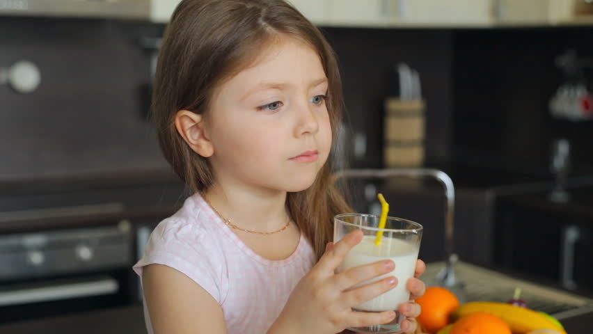 Little girl drinking milk through a straw from a glass