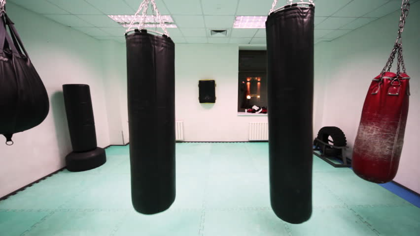 four different size punching bag hang in boxing training room, closeup