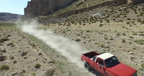 Aerial scene of car traveling on dirt road, dry, rocky, landscape. Monumental scenery. Car leves dust while driving. Starts near car ends far, high. Canyon of Piedra Parada, Patagonia Argentina.