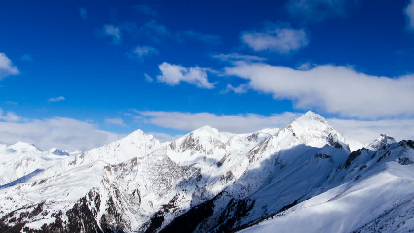 Beautiful alpine weather time lapse shot paning along the towering peaks of the Hohe Tauern mountain range in Tirol, Austria, during a sunny winter day.    Shutterstock HD Video #17239801