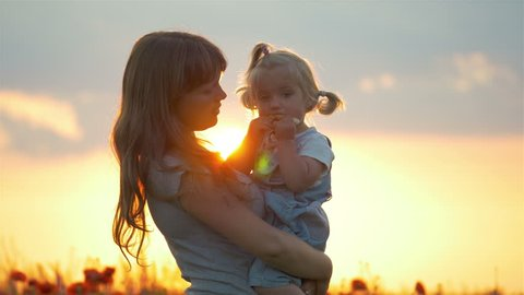 Mother hugs lovely child daughter in poppies field with sunset sunlight and flare effect