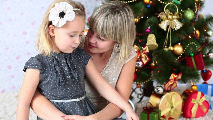 Mother kisses her daughter sitting on the floor near the Christmas Tree