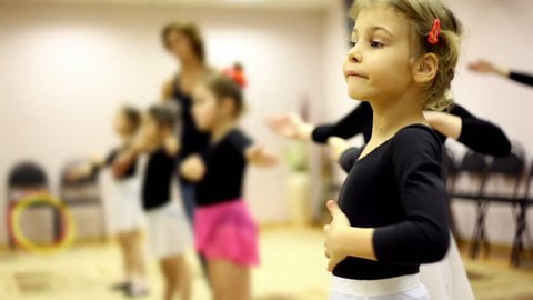 Girls learn how to dance with ballet teacher in recreation center