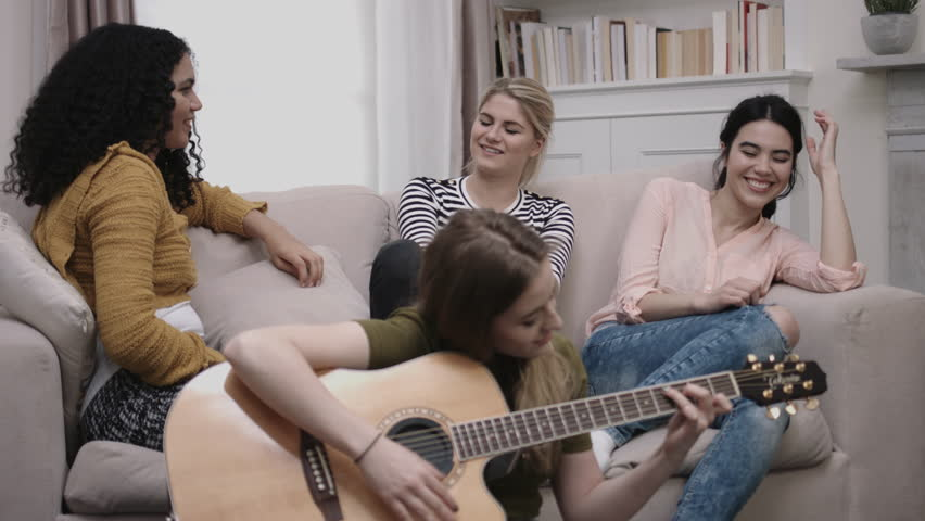 Group of female friends play guitar in student room
