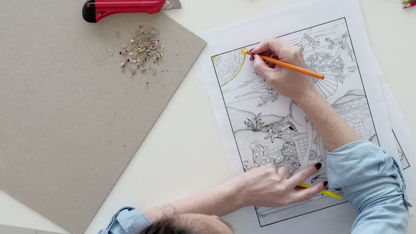 A professional asian architect is circling a tree symbol location top view of female hands coloring drawing in a book relaxing 4k stock malvernweather Image collections
