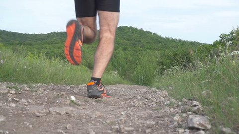 Slow motion.  Male runner exercising and training outdoors in nature. traill-running.