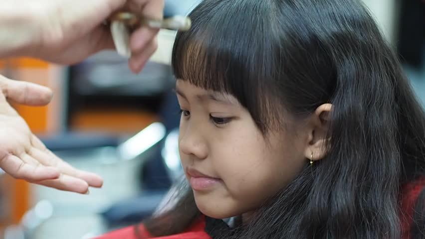 Little Asian girl getting haircut in hair salon | Shutterstock HD Video #17366554