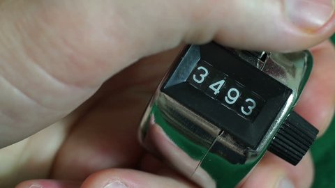 Close up macro shot of a mechanical hand operated tally counter used mainly for counting people entering an event or place or building.
