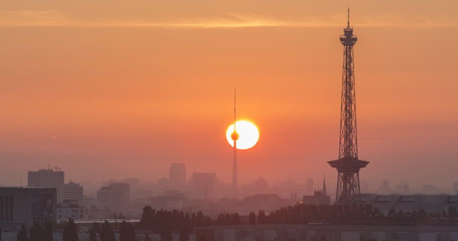 BERLIN, GERMANY - JUNE 2016: Sunrise in front of the silhouette of Berlin with the most famous towers and buildings. Time lapse view in 4K.
