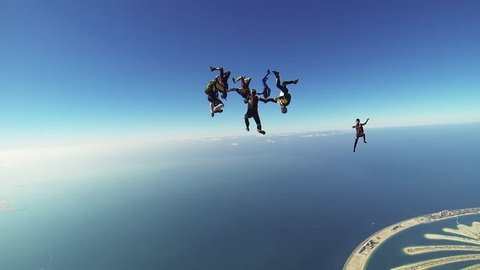 Professional skydivers parachuting above Dubai, make formation in sky. Sunny day. Extreme