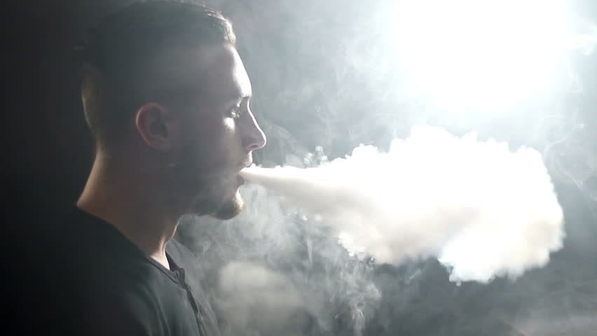 young vaper man exhaling big clouds of smoke with e-cigarette vape in slowmotion