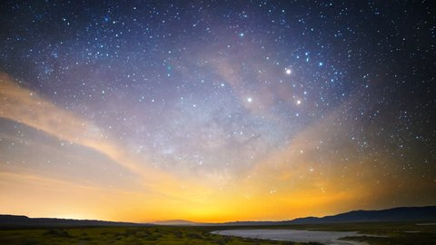 Astrophotography time lapse with motion of Milky Way galaxy & moon rising over Desert Gold wildflower super bloom 2016 in Carrizo Plain National Monument, California -Tilt Down-