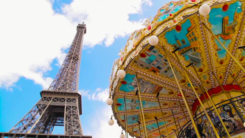 Gorgeous middle wide view on Eiffel tower first floor and vintage carousel in cloudy, blue sky. Romantic spring time in Paris, France.