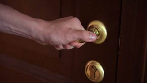 man hand open the door with the gilded handle