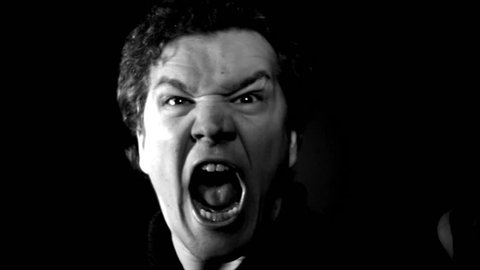 Furious yelling man in slow motion. This guy is so angry he's making an evil screaming rage face. Raging and livid, man moves in close with serious expression.