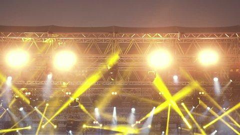 Stage lights,robotic spots,par,floodlights during live concert slomo 100p.Electronically controlled stage spotlights operating during a concert.100 fps slow motion low angle wide shot.