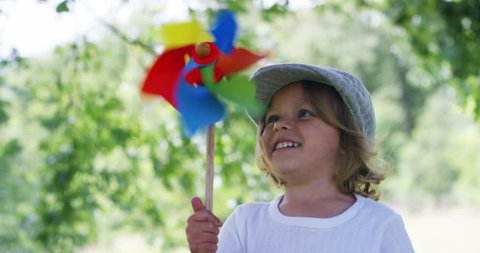 in a day of sun and wind, a happy little beautiful girl in green nature blows on a colorful pinwheel helped by the energy of fresh wind . concept of happiness and renewable wind energy.6k resolution