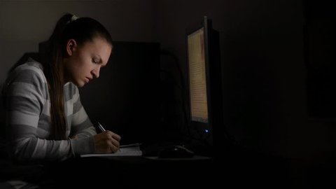 Young female business woman working at home.She works late into the night looking at monitor, Beautiful student preparing for the exam at night, girl studying at the night