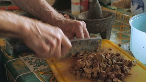 A man uses a meat cleaver to chop cooked chicken liver in slow motion for a passover seder dinner.