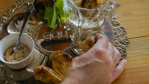 A hand adds a roasted hard boiled egg to a passover seder plate - dolly