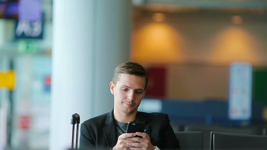 Urban business man talking on smart phone traveling inside in airport. Casual young businessman wearing suit jacket. Handsome male model. Young man with cellphone at the airport while waiting for | Shutterstock HD Video #17515714