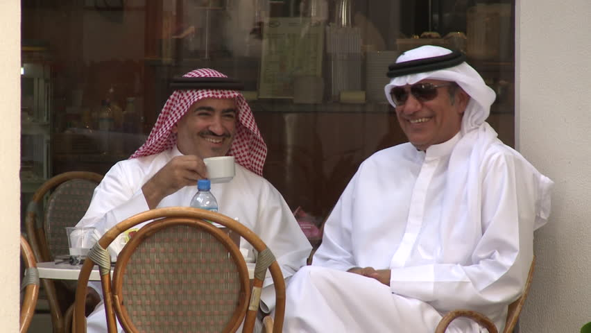 Abu Dhabi, UAE - circa 2013 - MCU of two Emirati men in traditional clothes, in a caf_, laughing over a cup of coffee.