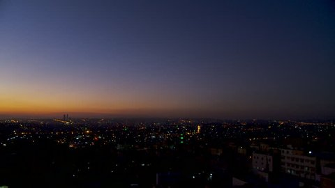 Sunset, Amman, Jordan. Pan-left across Amman's twinkling city lights as dusk turns into night. The sky is dark blue with orange and purple stripes across the horizon. (Amman, Jordan - 2016)