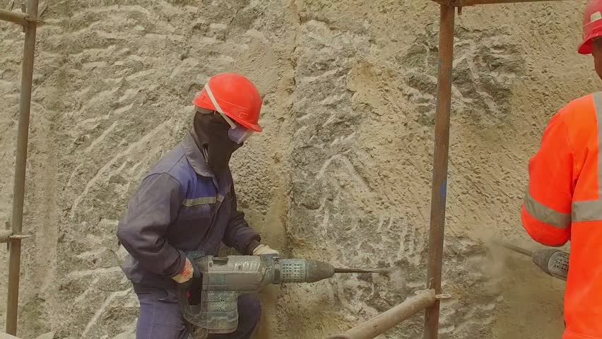 Worker hammer rock wall with jackhammer