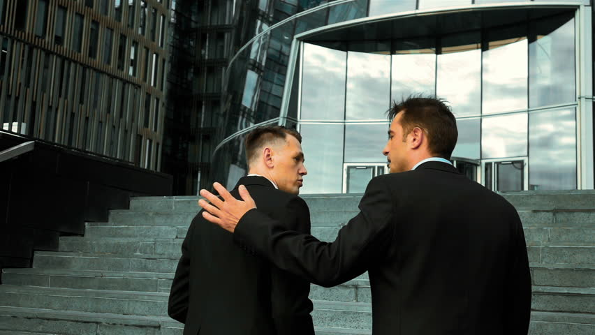 Slow motion. Colleagues and friends. Two cheerful businessmen pat on the shoulder and talking to each other while walking stairs outdoors. Glass Business centre bg.