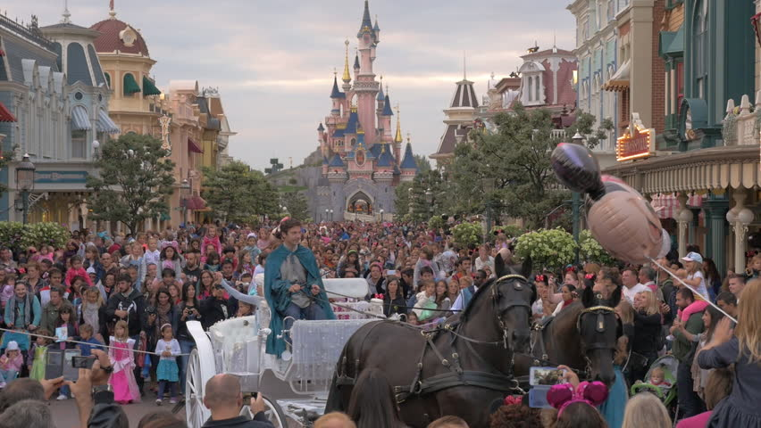 PARIS, FRANCE - SEPTEMBER 06, 2015: Characters of the cartoon Frozen riding in white carriage in Disneyland and crowd of people walking after them. Park receives around twelve million visitors a year