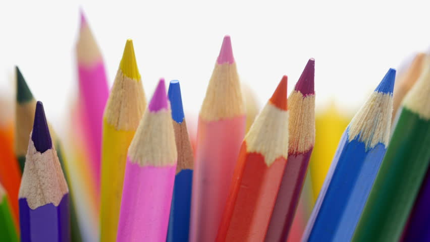 Top of color pencils. Color pencils turning on a white background. Close up. 4K footage.