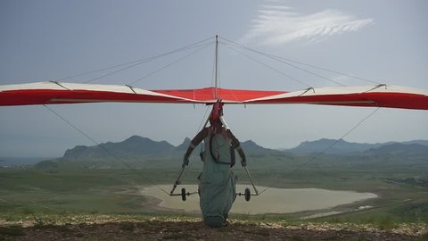 Hang glider takeoff on a background of lake