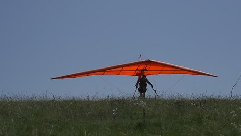 Takeoff of a hang glider in slow motion. Takes off the girl student of the flight school