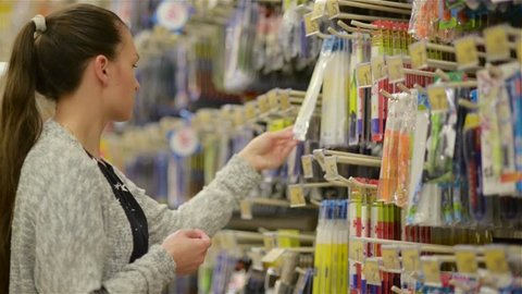 young beautiful woman buying stationery for school, beautiful mother choose pens and tools in a supermarket for her children, girl shopping in a supermarket