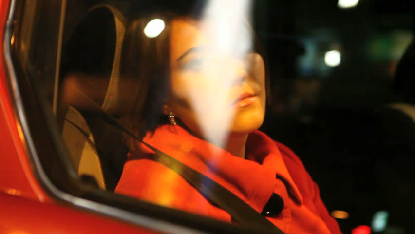 young woman in passenger seat of moving car