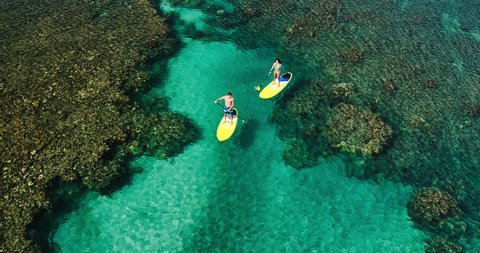 Aerial view of young couple stand up paddle boarding