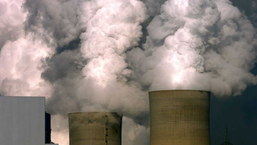 Close up shot of a huge lignite fired power plant's tall and dirty chimneys and steaming cooling towers.