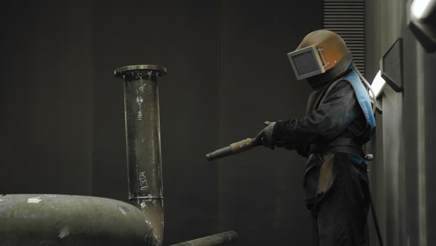 Worker Sandblasting Gas Pipe