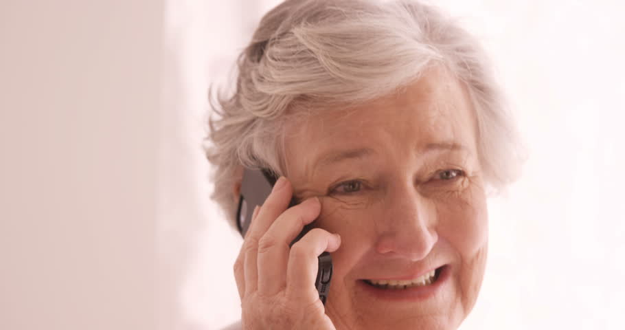 Senior Caucasian woman talking on mobile phone at home