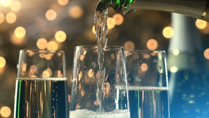 Champagne slow motion pour with Christmas lights and lens flare.