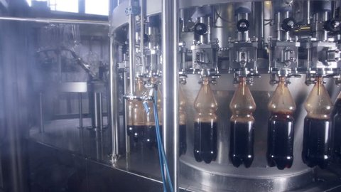 Pop and Soda pouring in bottles on fresh drinks production automated conveyor.