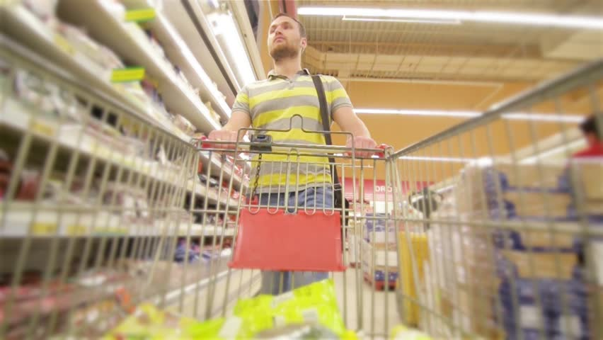 Guy with full supermarket trolley approaching camera, young man chooses products in the supermarket, man buys drinks in store | Shutterstock HD Video #17741137