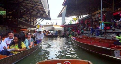 RATCHABURI, THAILAND - MAY 10 2016 : Trader selling food on boats at Damnoen Saduak floating market . Damnoen Saduak is a very popular tourist attraction in Thailand.