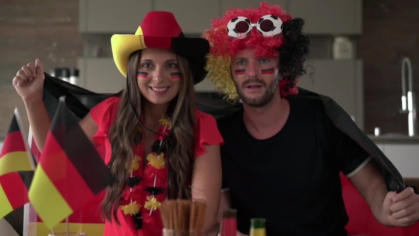 crazy german soccer fan couple thrilled and cheering for Germany in front of tv at home