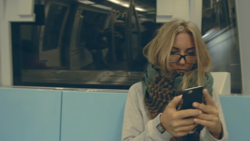 Young female hipster woman sitting in subway in Hong Kong, using smart phone. Pretty blonde teenage girl  with long hair, wearing  glasses and huge scarf going in underground. | Shutterstock HD Video #17793826