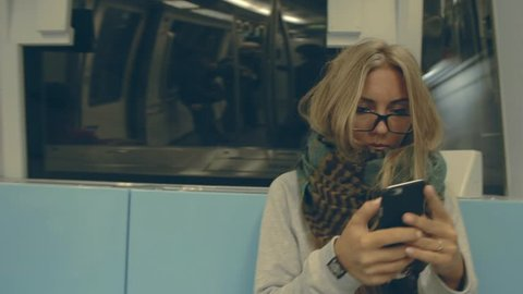 Young female hipster woman sitting in subway in Hong Kong, using smart phone. Pretty blonde teenage girl  with long hair, wearing  glasses and huge scarf going in underground.